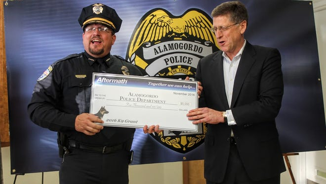 Alamogordo Chief of Police Daron Syling shares a laugh with Aftermath Services CEO Doug Berto as he receives the $5,000 grant the department won through Aftermath Services annual K-9 contest Thursday.