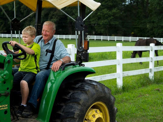 Emory Foster, 6, takes the wheel of his granddad Gary Lockhart's John Deere tractor after a morning visit.  Tractors are the leading cause of farm-related fatalities involving youth.