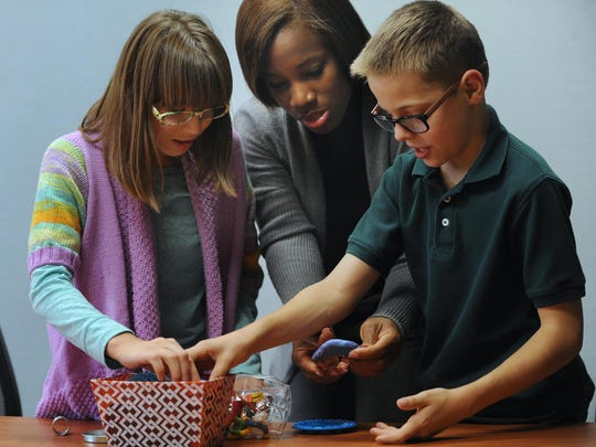 Stacey Gibson, center, a trauma assessment specialist, works with Gabby, 13, and Duncan, 11, after talking to their parents about test results at the Easter Seals Michigan office in Center Line. Duncan, who was adopted along with his sister from Russia, is a borderline asthmatic, and his mother believes it's related to trauma earlier in his life.