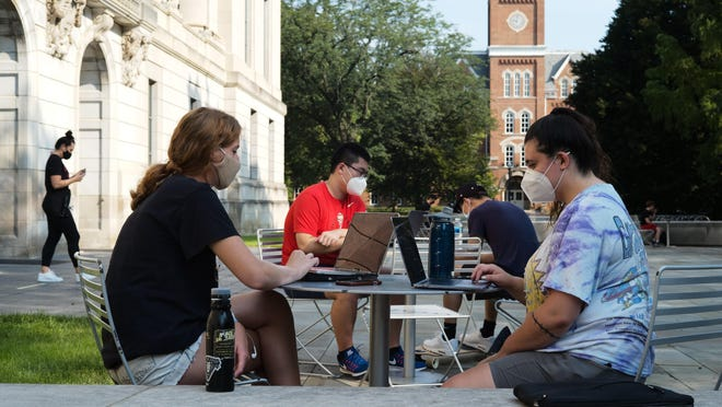 Friends Jessica DeSena, right, and Camden Coggburn stay busy during the first day of fall classes on Tuesday at Ohio State University. The school is using a mix of virtual and in-person learning because of the ongoing COVID-19 pandemic.