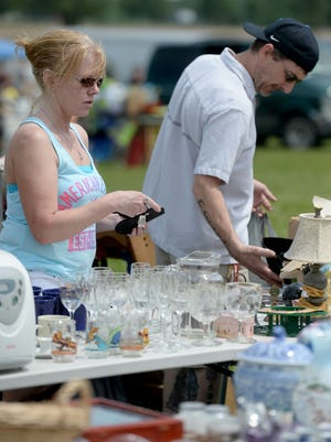 Jennifer Burns, left, and Ed Barnes look for items that interest them in Centerville on the first day of the 2015 Historic National Road Yard Sale along U.S. 40 in Wayne County.