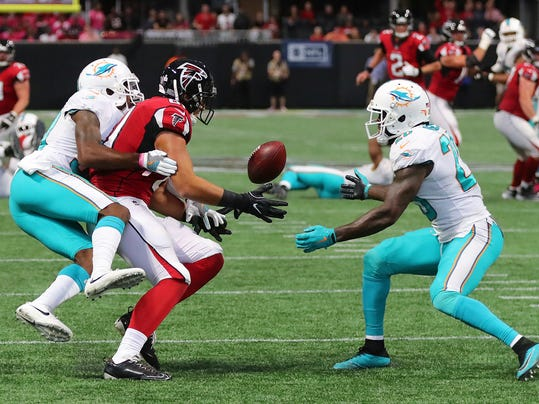 Miami Dolphins cornerback Cordrea Tankersley, left, hits Atlanta Falcons tight end Austin Hooper, knocking the ball loose for a interception by Dolphins safety Reshad Jones, right, during the final minute of an NFL football game Sunday, Oct. 15, 2017, in Atlanta. (Curtis Compton/Atlanta Journal-Constitution via AP)