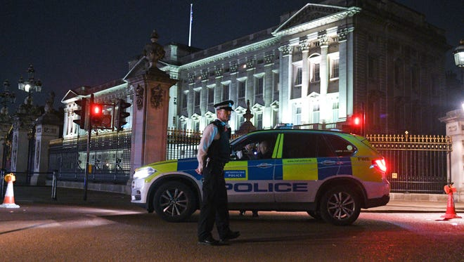 Police teams secure the roads behind a cordoned area following an apparent attack on two police officers at Buckingham Palace on Aug. 25, 2017 in London.