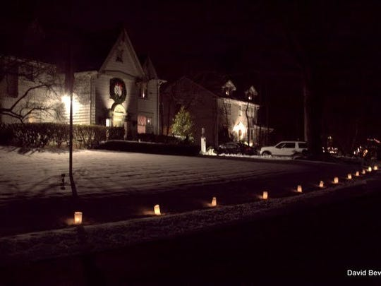 Lights line a street as part of the Netherwood Heights Historic District's annual Christmas Eve luminary displays in Plainfield.