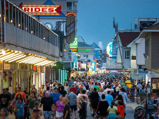 The Boardwalk in Ocean City bustles at night with people moving about and performers entertaining passersby. The Boardwalk in Ocean City bustles at night with people moving about and performers entertaining passersby.
