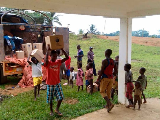 People unload boxes of meals prepared by Kids Fighting