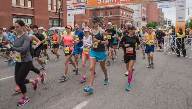 Runners pass the starting line on Main Street after the start of the Kentucky Derby Festival Marathon miniMarathon.