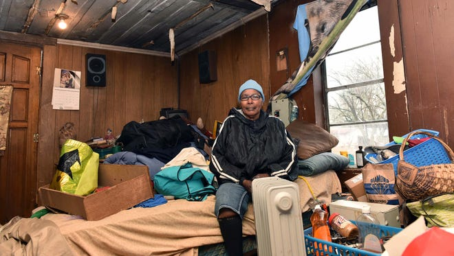 Clara Daniel of Edwards, Miss., sits in the makeshift bedroom of her dilapidated home. She moved her bed into the living room four years ago after the floor in her bedroom began to collapse.