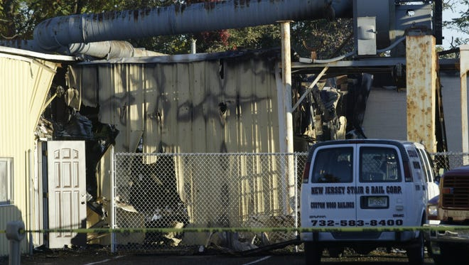 Investigators discuss the fire at the United States Mahogany Corporation, in Aberdeen, Sunday morning, Oct. 18, following a Saturday evening fire.