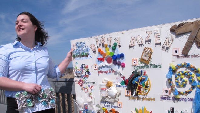 Erin O'Neill, a student volunteer with the Clean Ocean Action environmental group, holds a poster on Monday April13, 2015 in Sandy Hook, N.J. showing some of the items of trash that volunteers removed from New Jersey's beaches last spring and fall. Plastic pieces accounted for 13 percent of the 315,000 items removed from the sand last spring and fall. Unusual items found along the shoreline included a whoopee cushion, bra padding, a stun gun and a clay sculpture of the baby Jesus.