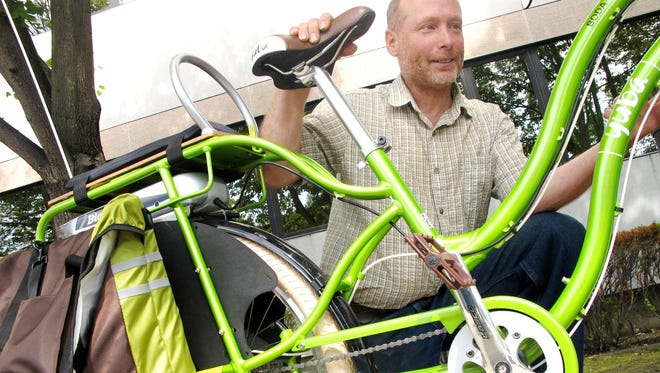 Green glow: Dave Cohen, founder of Brattleboro-based nonprofit VBike, displays a Yuba elBoda Boda model cargo bicycle at the Vermont Agency of Transportation headquarters in Montpelier. The bicycle's rechargeable battery lies beneath the cargo/passenger deck.