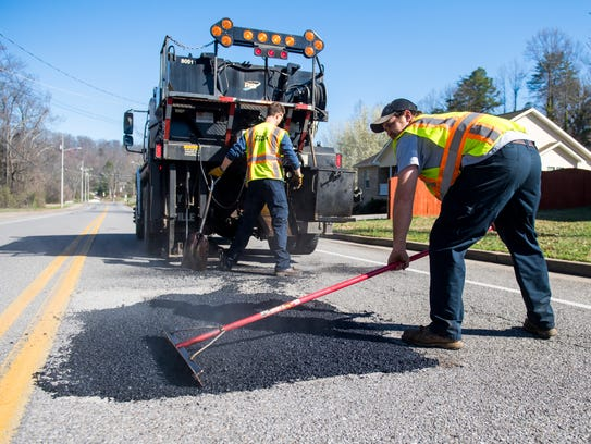 A crew patches a pothole on Bradshaw Road in front