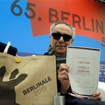 Dieter Kosslick director of the International Film Festival Berlin, the Berlinale, holds a copy of a 65 years old Golden Bear award certificate as he poses for the media prior to the annual program press conference in Berlin, Germany, Tuesday. The 65. Berlinale will take place in the German capital from Feb. 5-15.