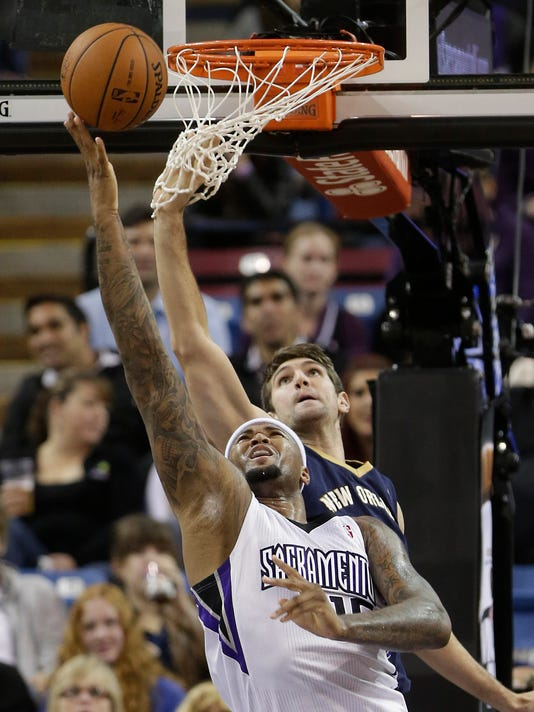 Sacramento Kings center DeMarcus Cousins, foreground, goes to the basket against New Orleans Pelicans center Jeff Withey during the first quarter of an NBA basketball game in Sacramento, Calif., Monday, March 3, 2014.(AP Photo/Rich Pedroncelli)