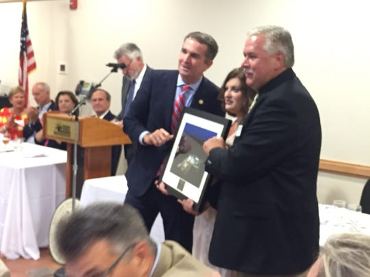 Gov. Ralph Northam presents the Chairman's Award to David and Penny Fluhart representing the Wachapreague Vol. Fire Company at the Eastern Shore of Virginia Chamber of Commerce annual meeting on Monday, July 23, 2018 in Melfa, Virginia.