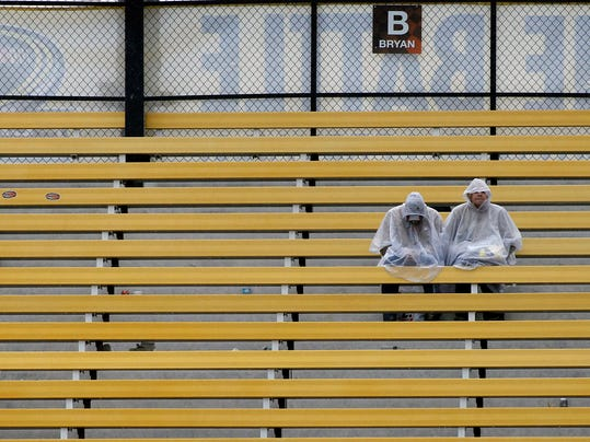A pair of fans sit in the rain as they wait for the NASCAR Sprint Cup Series auto race at Phoenix International Raceway, Sunday, Nov. 15, 2015, in Avondale, Ariz. (AP Photo/Ralph Freso)