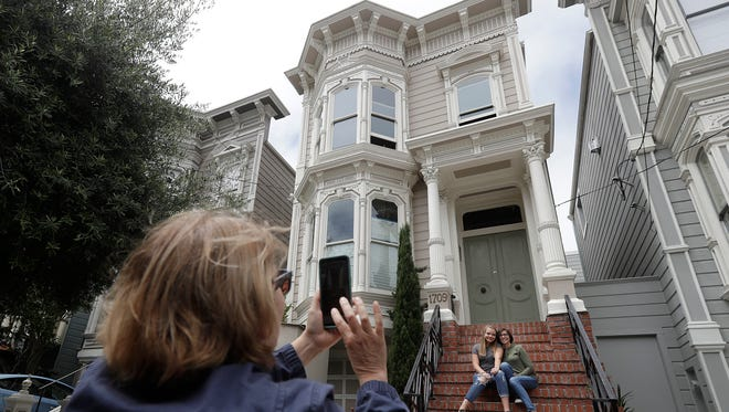 "Aries Layton, seated left, and her aunt Kelsy Layton pose as Debra Layton, Aries' grandmother and Kelsy's mother, foreground, takes photos outside a Victorian home made famous by the television show ""Full House"" in San Francisco, Tuesday, July 17, 2018. Tour buses will no longer be swinging by the San Francisco house made famous in the popular 1990s sitcom ""Full House."""