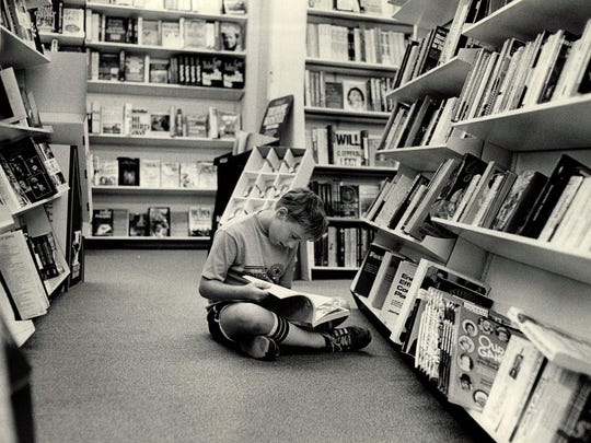 Chris Ritter, 13, gets absorbed in a book at Village Green Bookstore in this 1980 photo.