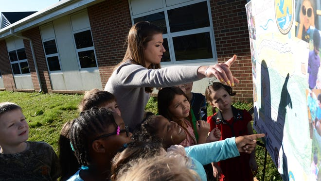 Kegotank Elementary School 1st grade teacher Morgan Crockett points out features of the Schoolyard Habitat outdoor classroom project on a site plan to her students on Friday, March 18, 2016. The U.S. Fish and Wildlife Service is partnering with Accomack County Public Schools and other community partners to establish the outdoor teaching space. The school held a groundbreaking ceremony on Friday.