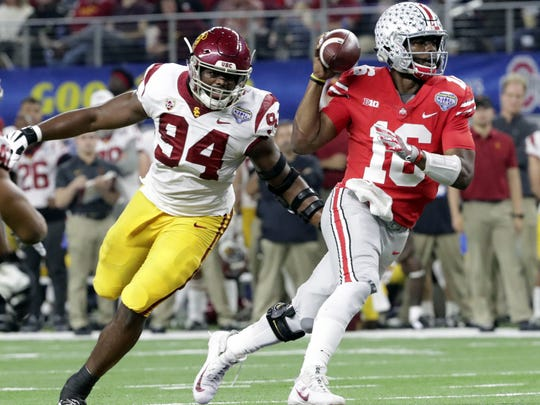 Ohio State quarterback J.T. Barrett (16) is chased by Southern California defensive tackle Rasheem Green (94) during the first half of the Cotton Bowl NCAA college football game in Arlington, Texas, Friday, Dec. 29, 2017. Barrett, from Wichita Falls, scored two touchdowns in the 24-7 Ohio State victory. It was his record 38th (38-6) as an Ohio State starter.