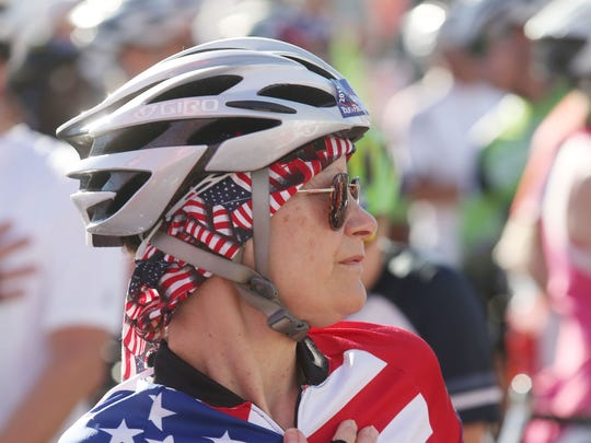 A bike rider listens to the national anthem before the start of the race.