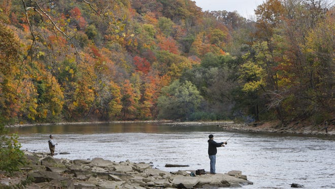 Anglers cast out from both sides of the river while fishing the Genesee River.