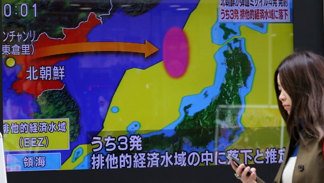 A woman walks past a screen showing a TV news on a missile firing by North Korea with a map of Japan and North Korea in Tokyo, Monday, March 6, 2017.
