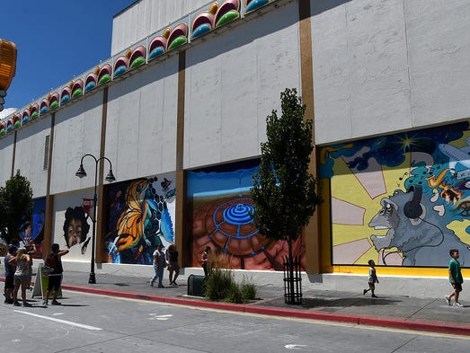 People pass by finished murals following the Circus
