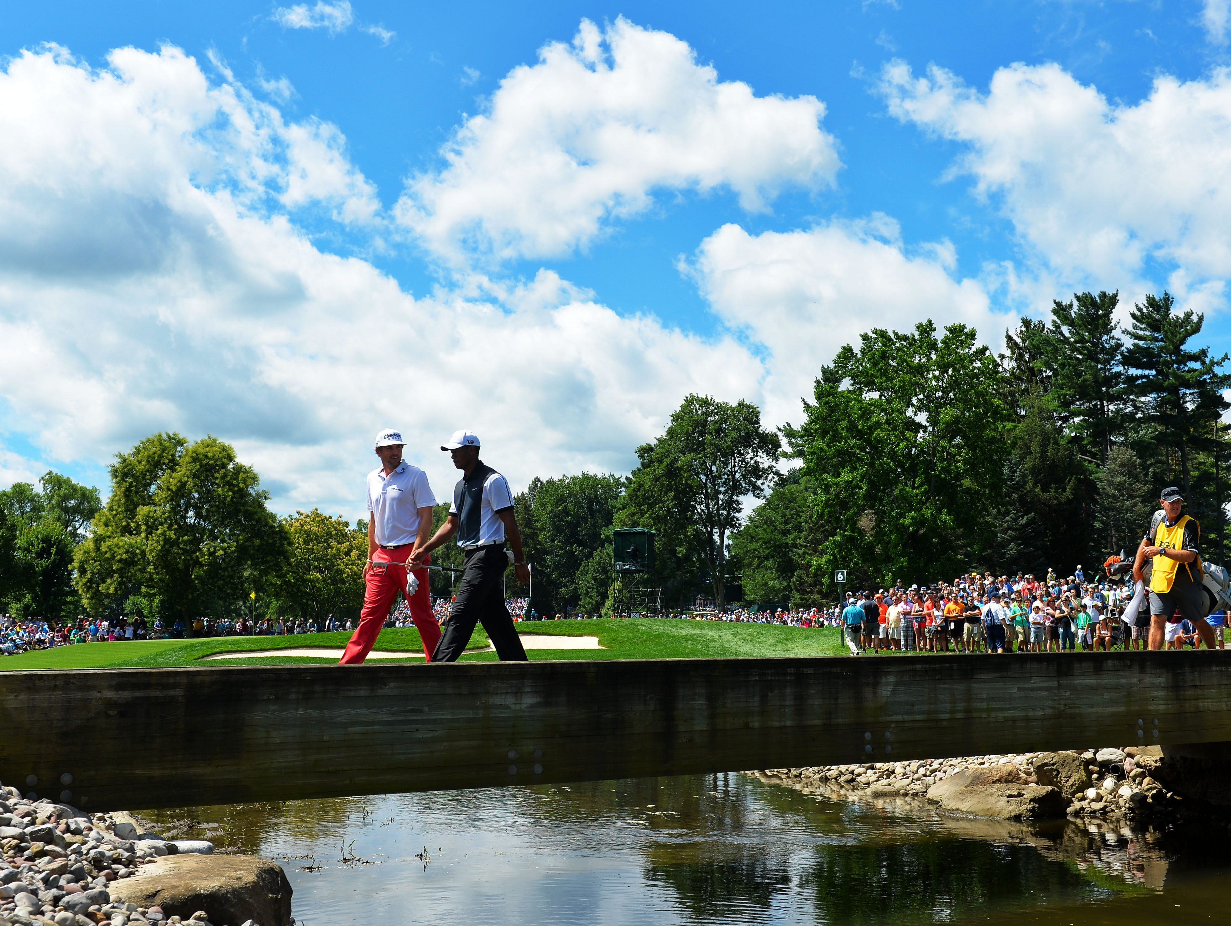 Keegan Bradley and Tiger Woods cross a bridge on the sixth hole.