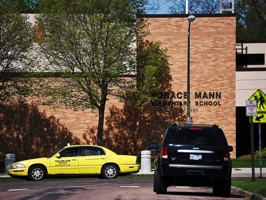 A Yellow Cab taxi pulls away from Horace Mann Elementary