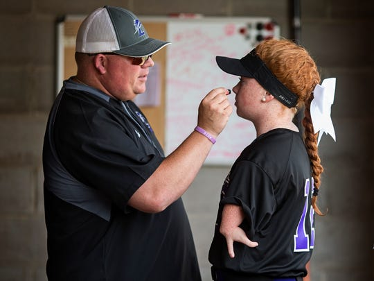 """Eric Pavey, left, Katelyn's father and softball coach, puts eye paint onto her cheeks before every game. The father wrote a touching piece to her for senior night as a tribute to their bond through softball. """"You would be waiting every day to go in the backyard to hit and throw and you didn't want to come back in even at dusk, you insisted there was a night to continue playing,"""" the piece read. """"You insisted, and your insistence would win, and we stayed outside to play catch."""" May 18, 2017"""