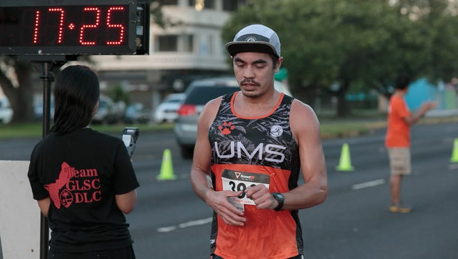 Derek Mandell crosses the finish line to be the first male finisher for the Guam Legal Services Corporation Disability Law Center Let's Keep Access to Justice 5K Run, Walk, or Wheel Event held at Chamorro Village in Hagåtña on Oct. 10.