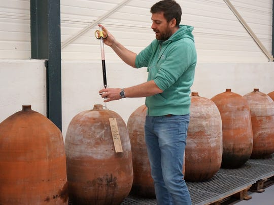 Maison Ventenac winemaker Olivier Rame pulls a sample of syrah from terra-cotta eggs at his winery in Langeudoc.
