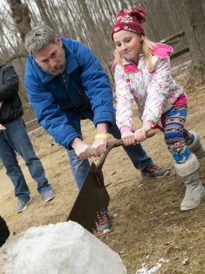 Joe McAdams of Vernon, and daughter Tara, try out an ice saw on a block of ice. Fosterfields Living Historical Farm hosts ÒA WinterÕs Day on the FarmÓ that includes wagon rides, wood sawing, ice sawing and plenty other activities that would have taken place during the time of Caroline Foster, the last owner.