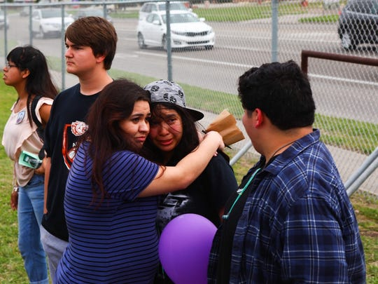 King High School students console one another Wednesday, March 28, 2018, during a vigil for Rai-ane Garza, 16, who was killed by a hit-and-run driver Tuesday, March 27, 2018, just off campus. The students gathered near the fence along Staples Street near the intersection with Mustang Trail.