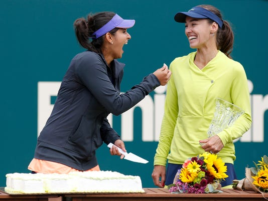 FILE - In this Sunday April 12 2015 file photo Sania Mirza, left, of India, jokes with her teammate, Martina Hingis, of Switzerland, after defeating Alla Kudryavtseva and Anastasia Pavlyuchenkova during a doubles final match at the Family Circle Cup tennis tournament in Charleston, S.C. After a 15-year absence, Martina Hingis once again played and won a women's doubles match at the French Open. (AP Photo/Mic Smith, File)