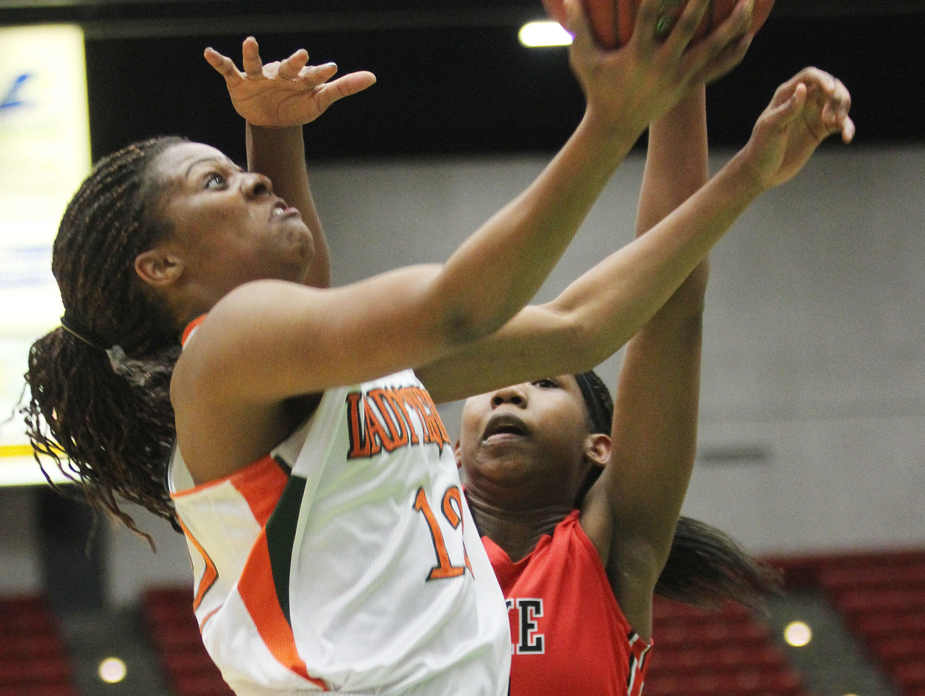 Dunbar's Kiara Desamours shoot a lay-up under the defense of Lake Highland's Koi Love during the Class 4A state championship game at the Lakeland Center.