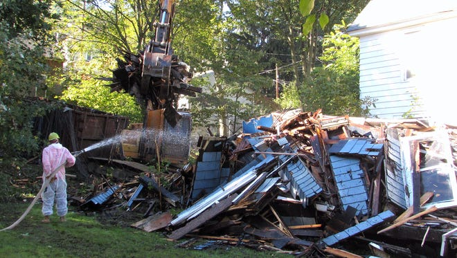 A crew from Swarthout Recycling demolishes an arson-damaged house on East Third Street in Corning on Monday.