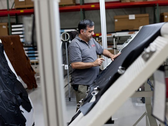 Employees work on a large piece of leather before it