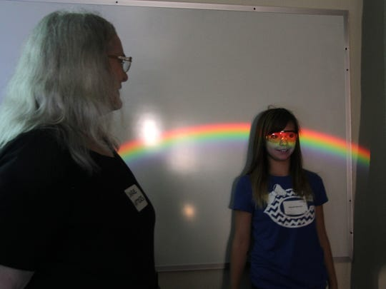 A Sixth Grade Academy student observed the colors in the visible spectrum as nuclear physicist Laurie Waters watched at the Expanding Your Horizons Conference.