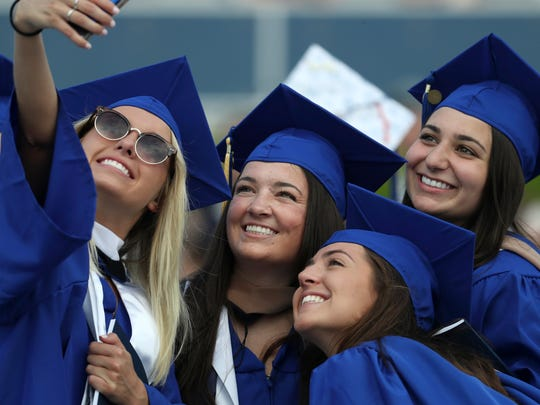 Students gather for a photograph as the University of Delaware hosts commencement ceremonies for approximately 6,200 graduates at Delaware Stadium in May 2018.