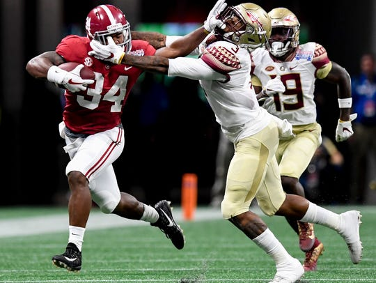Alabama running back Damien Harris (34) is slowed by