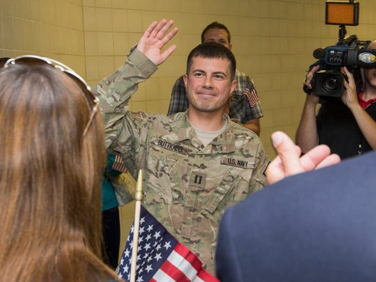 South Bend Mayor Pete Buttigieg smiles and waves as he is greeted by family and friends Thursday, September 25, 2014, at Concourse A at South Bend International Airport in South Bend after returning from a seven-month tour serving in the U.S. Navy in Afghanistan.