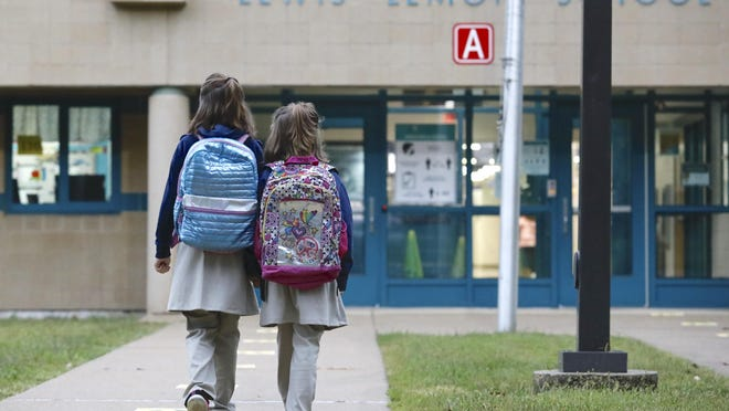 Rockford Public Schools reopened Tuesday. Melody Johnson, left, 9, and her sister Miranda Johnson, 6, both of Rockford, walk toward Lewis Lemon Elementary School for the first day of class.