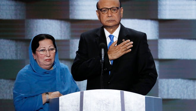 FILE - In this Thursday, July 28, 2016 file photo, Khizr Khan, father of fallen US Army Capt. Humayun S. M. Khan and his wife Ghazala speak during the final day of the Democratic National Convention in Philadelphia. Republican presidential nominee Donald Trump broke a major American political and societal taboo over the weekend when he engaged in an emotionally-charged feud with Khizr and Ghazala Khan, the bereaved parents of a decorated Muslim Army captain killed by a suicide bomber in Iraq. He further stoked outrage by implying Ghazala Khan did not speak while standing alongside her husband at last week's Democratic convention because they are Muslim. (AP Photo/J. Scott Applewhite, File)