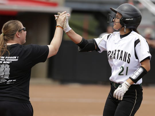 Oshkosh North High School's Shaye Gauthier gives first base coach Taylor Loew a high five after a hit during their game on June 8, 2017. Oshkosh North played Kaukauna in the WIAA Division 1 quarterfinal softball game at UW's Goodman Diamond in Madison, Wis. Kaukauna won 2-0 to advance.