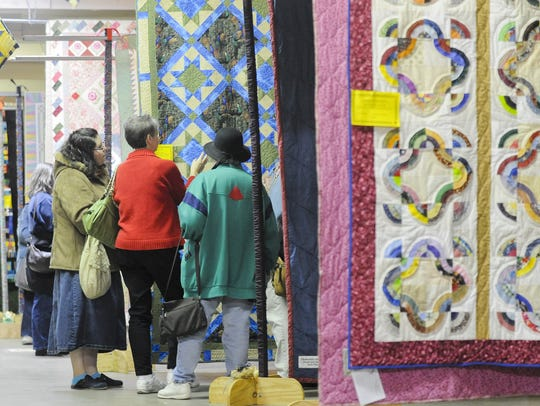 Hanging quilts line the floor during the 2011 Quilt