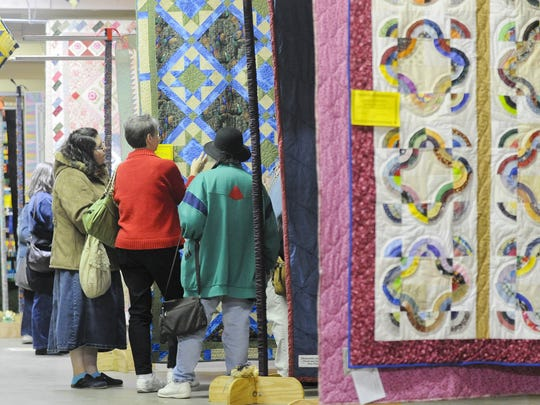 Hanging quilts line the floor during the 2011 Quilt Show.