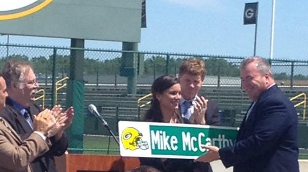 Green Bay Packers coach Mike McCarthy, right, receives the Mike McCarthy Way street sign during a ceremony in Ashwaubenon on Wednesday. He's accompanied by his daughter Alex and Packers president Mark Murphy.