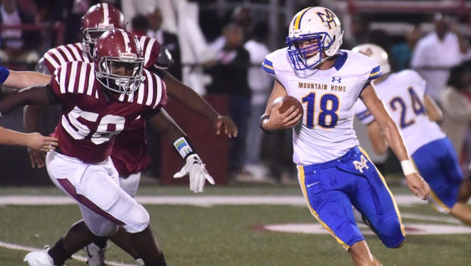 Mountain Home's Seth Beshears carries the ball against Pine Bluff on Friday night.
